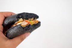 Äta den svarta hamburgaren Arkivfoton