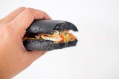 Äta den svarta hamburgaren Royaltyfri Foto