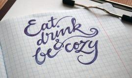 Äta, drinken och var hemtrevlig calligraphic bakgrund fotografering för bildbyråer