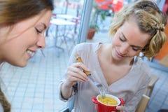 Äta efterrätten med vännen Arkivbild