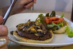 Äta en hamburgare på plattan med bestick royaltyfria foton