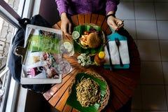 Äta en organisk sund mat på den trärunda tabellen Det finns spagetti med svartpeppar som tjänar som på det gröna bananbladet royaltyfri foto