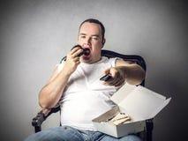 Äta ett stycke av kakan framme av tv:n Arkivfoton