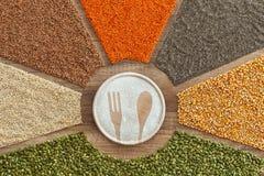 Äta ett sunt och olikt banta - färgrika korn som omger det runda brädet med gaffel- och skedform royaltyfri fotografi