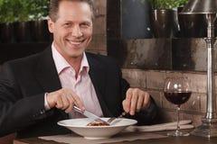 Äta för affärsman. Säkra män i formella kläder som äter på ret Royaltyfri Foto