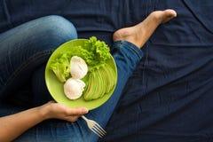 äta för begrepp som är sunt Kvinna` s räcker innehavplattan med grönsallat, avokadoskivor och tjuvjagade ägg Royaltyfria Foton