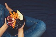 äta för begrepp som är sunt Kvinna` s räcker innehavplattan med päron, druvor, persimon, och granatäpplet bär frukt royaltyfri fotografi