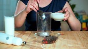 äta för begrepp som är sunt På tabellen mjölkar en blandare, i ett exponeringsglas, bär i en platta arkivfilmer