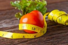 äta för begrepp som är sunt Tomat med den måttbandet, gaffeln och grönsaken med måttbandet på träskrivbordet arkivbild