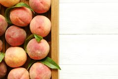 äta för begrepp som är sunt Trämagasin som staplas fullständigt med fullvuxna organiska mogna persikor för lokal jordbruksprodukt arkivfoto