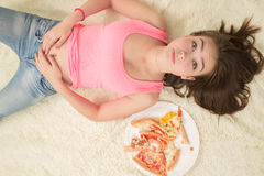 Äta för mycket att ligga för flicka Royaltyfri Foto