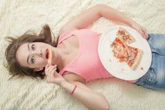 Äta för mycket att ligga för flicka Royaltyfria Bilder