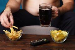 Äta för mycket mannen som sitter på soffan med tvfjärrkontrollen royaltyfria foton