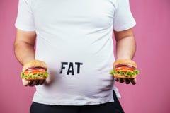 Äta för mycket snabbmat, frossare, skräpmat arkivfoto