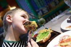 äta för pojkehamburgare arkivbilder