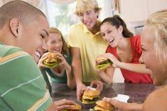 äta för pojkehamburgare som är tonårs- arkivfoton