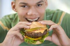 äta för pojkehamburgare som är tonårs- Fotografering för Bildbyråer