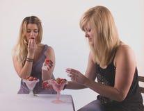 Äta för två gladlynt flickor jordgubbar med nöje Royaltyfri Foto