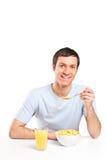 Äta för ung man som är sädes-, och dricka orange fruktsaft Arkivfoto