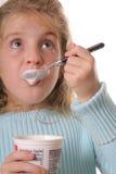 äta flickan som upp ser vertikalt yoghurtbarn Royaltyfri Bild