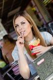 Äta fransman steker i härlig blond ung kvinna för för snabbmatcoffee shop eller restaurang med gröna ögon som har gyckel, stående Royaltyfri Foto