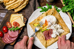 Äta frukosten: kräppgalette, tjuvjagat ägg, skinka, avokado och ost Arkivbild