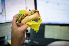 Äta frukosten på arbete framme av datorskärmen arkivbilder
