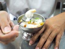 Äta glass som strilas med jordnötter och kokosnöten, mjölka den royaltyfri bild