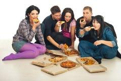 äta grupperar vänner pizza arkivbild