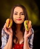 äta hamburgarekvinnan Flickatugga av den mycket stora hamburgaren Royaltyfri Bild