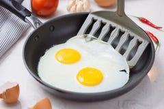 Äta i processen, stekte ägg i en stekpanna för frukost royaltyfri fotografi