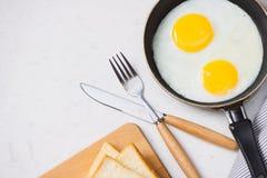 Äta i processen, stekte ägg i en stekpanna, rostat bröd och eller royaltyfria foton
