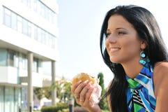 äta kvinnabarn för hamburgare utomhus Royaltyfria Foton