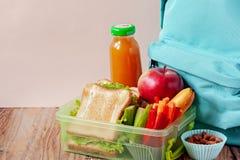 Äta lunch asken med aptitretande mat och ryggsäcken på trätabellen fotografering för bildbyråer