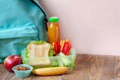 Äta lunch asken med aptitretande mat och ryggsäcken på trätabellen arkivbild