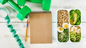 Äta lunch asken med kokta ägg, havremjölet, avokadot, mikrogräsplaner och frukter fotografering för bildbyråer