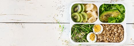 Äta lunch asken med kokta ägg, havremjölet, avokadot, mikrogräsplaner och frukter arkivfoton
