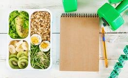 Äta lunch asken med kokta ägg, havremjölet, avokadot, mikrogräsplaner och frukter royaltyfria bilder