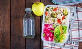 Äta lunch askhöna, broccoli, gröna ärtor, tomaten med ris och röd kål royaltyfri bild