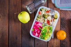 Äta lunch askhöna, broccoli, gröna ärtor, tomaten med ris och röd kål arkivbilder