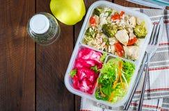 Äta lunch askhöna, broccoli, gröna ärtor, tomaten med ris och röd kål arkivbild