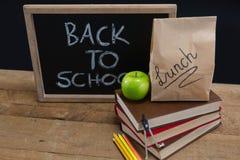 Äta lunch den pappers- påsen, göra grön äpplet och kritisera med text tillbaka till skolan på trätabellen Arkivbilder