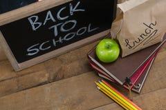 Äta lunch den pappers- påsen, göra grön äpplet och kritisera med text tillbaka till skolan på trätabellen Fotografering för Bildbyråer