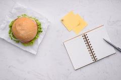 Äta lunch i regeringsställning, den läckra hemlagade hamburgaren på tabellen royaltyfri bild
