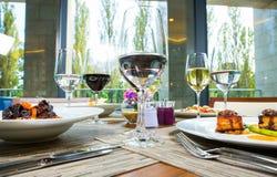 Äta lunch i restaurangen, exponeringsglas av vin med vitt och rött Variation av disk, kött, skaldjur, grönsaker, grönsallat arkivbilder