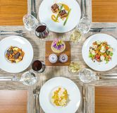 Äta lunch i restaurangen för fyra personer, exponeringsglas av vin med vitt och rött Variation av disk, skaldjur, grönsaker Royaltyfria Foton