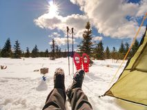 Äta lunch matlagning och mannen som vilar under vinterslinga Snöskor och poler Fotografering för Bildbyråer