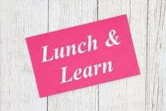 Äta lunch och lär text på rosa kort arkivfoton