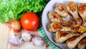 Äta lunch stekt kycklingben och grönsaker på trätabellen Arkivbild