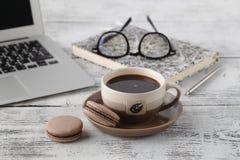 Äta lunch tid på kontorsarbetsplatsen med makron för kaffeanв royaltyfri foto